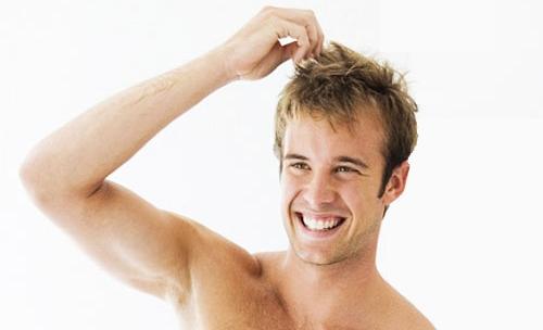 довольный мужчина трогает свои волосы